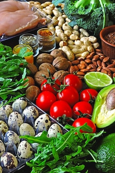ケトジェニックダイエットのコンセプト。低炭水化物ケトダイエットの製品セット。緑の野菜、ナッツ、鶏の切り身、亜麻の種子、ウズラの卵、チェリートマト。健康食品のコンセプト。ケトダイエット食品。