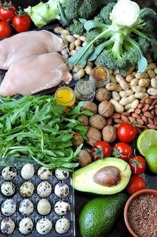 Набор продуктов низкоуглеводной кето диеты. зеленые овощи, орехи, куриное филе, семена льна, перепелиные яйца, помидоры черри.