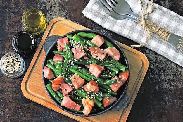 Зеленая фасоль с беконом в сковородке чугуна. концепция здорового питания. кето диета. пеганская диета. палео диета.