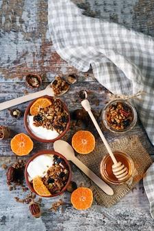 健康的な朝食やデザート。グラノーラとみかんのヨーグルト。自家製グラノーラ。はちみつ。フラット横たわっていた。