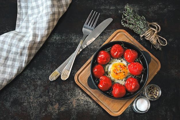 Яйцо запеченное с помидорами черри и тимьяном в чугунной сковороде.