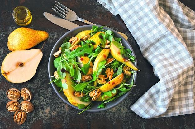 Салат с рукколой, грушей и грецким орехом. веганская миска красочного салата. красочная, здоровая пища.