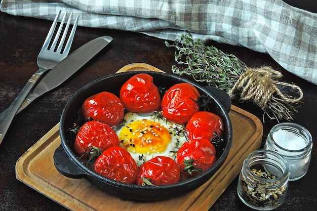 Яйцо запеченное с помидорами черри и тимьяном в чугунной сковороде. здоровый завтрак. кето завтрак.