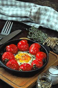 チェリートマトとタイムを鋳鉄製のフライパンで焼いた卵。健康的な朝食。ケト朝食。