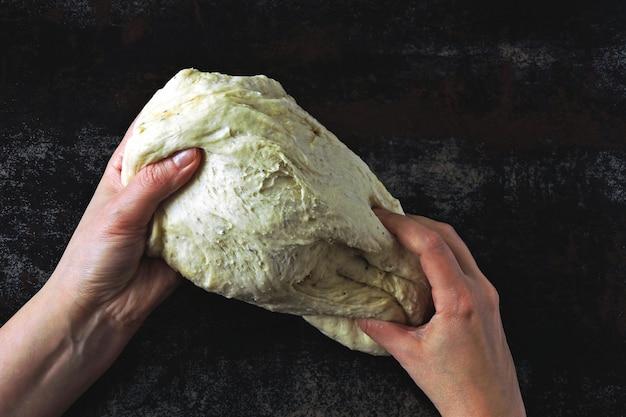 Дрожжевое тесто в женских руках на темном фоне.
