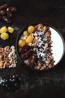 Чаша для завтрака с греческим йогуртом, овсянкой, мюсли и сухофруктами.