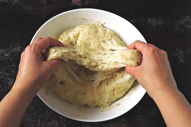 Мягкое тесто в руках повара.