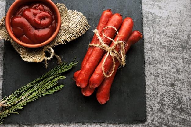 Копченые колбаски с соусом и розмарином. вид сверху.
