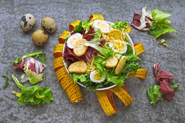 Концепция диетического питания. здоровый салат с перепелиными яйцами и зелеными листьями. измерительная лента. концепция похудения с помощью питания.