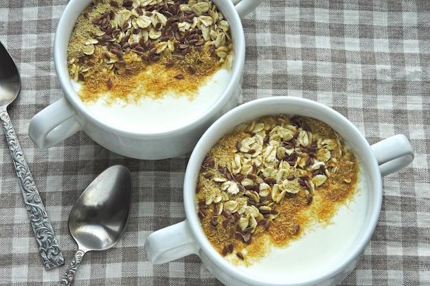Две миски с белым йогуртом, отрубями и семечками. здоровый завтрак. диетическое питание.