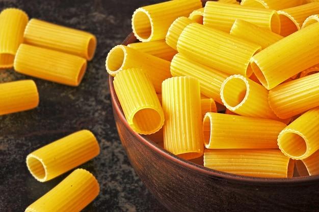 Сырье ригатони макароны в миску.