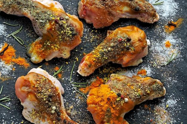 Сырые куриные крылышки, маринованные в специях на черной каменной доске.