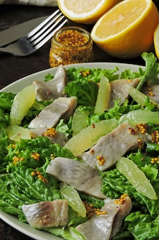 緑の葉、ニシン、レモンのヘルシーサラダ。レモンとニシンのサラダ。ケトダイエット。ヘルシーなランチまたはディナー。