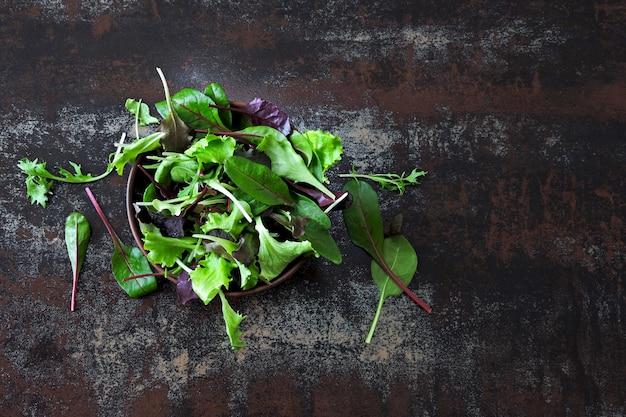 ボウルにベビーサラダを混ぜます。健康食品や食事療法の概念。スーパーフードエコフード。フィットネス食品。