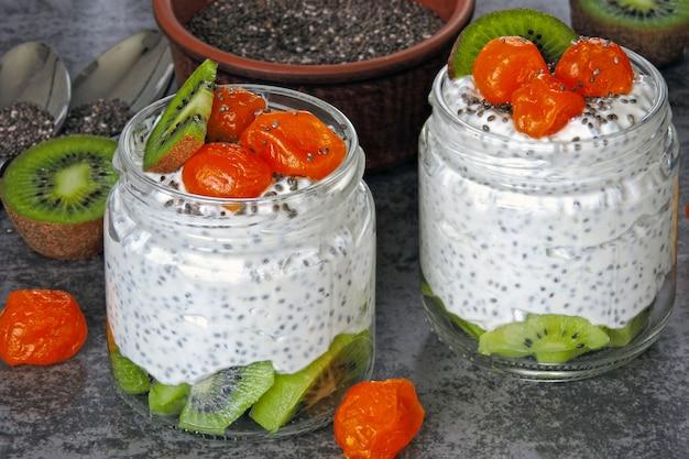 Йогурт с чиа, киви и кумкватом. белый йогурт с фруктами в банках. фитнес завтрак. здоровая пища. кето диета.