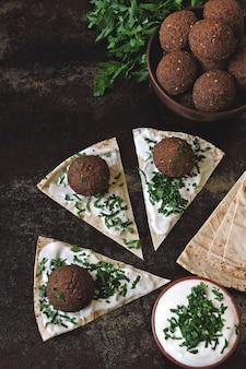 新鮮なファラフェルボール、ピタ、ソース、ハーブ。ビーガンファラフェル。健康的な赤身の食べ物。中東料理。