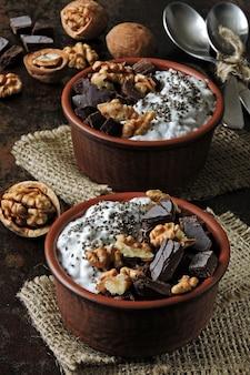 Две чашки с йогуртом с семенами чиа, грецкими орехами и темным шоколадом. завтрак или десерт на двоих. здоровая пища.