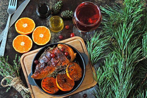 クリスマスディナー。みかんとクランベリーで焼いた鶏の胸肉。クリスマスツリーの枝とワインのグラス。
