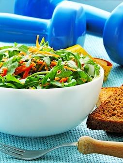 フィットネスサラダ、ダンベル、メジャーテープ。減量と健康的なライフスタイルの概念。