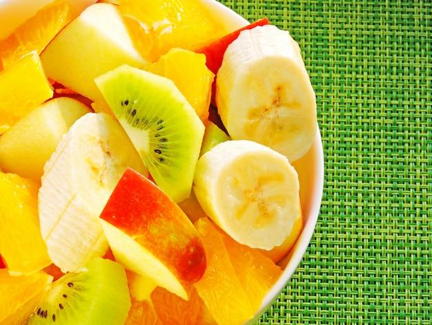 Чаша фруктовый салат. фруктовый салат с киви, бананом, апельсином и яблоком. концепция фитнес-питания.