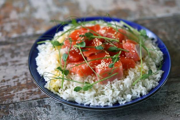 Тарелка с рисом, лососем и микро зеленью.