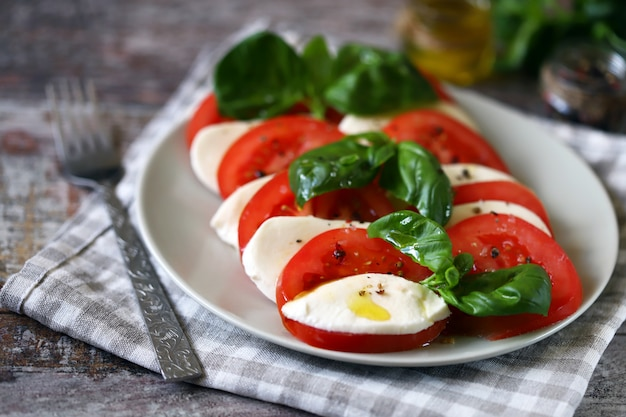 トマトのモッツァレラチーズとバジルの伝統的なカプレーゼサラダ。