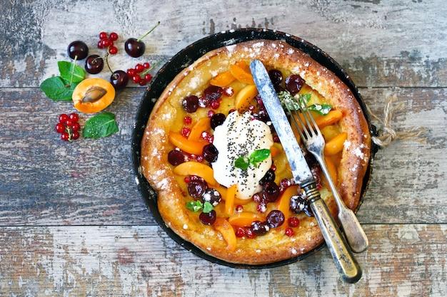フルーツとベリーのオランダの赤ちゃんパンケーキ。健康的な朝食。フードトレンドデザート。
