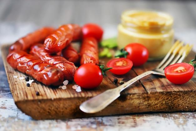 Аппетитные жареные копченые колбаски на деревянной доске.