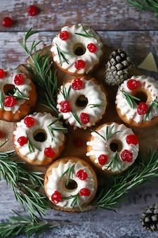 Рождественские кексы с розмарином, белой глазурью и красными ягодами. элегантные праздничные торты. рождественская композиция.