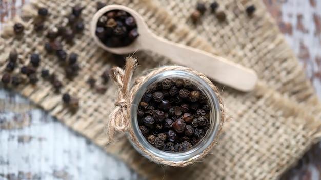 瓶と木のスプーンの黒胡椒