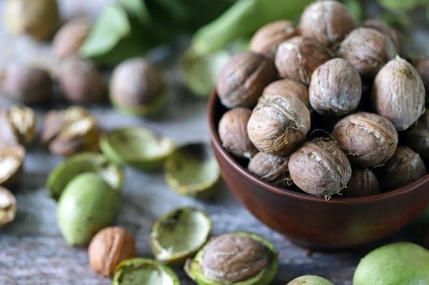 Грецкие орехи в миску. листья грецкого ореха.