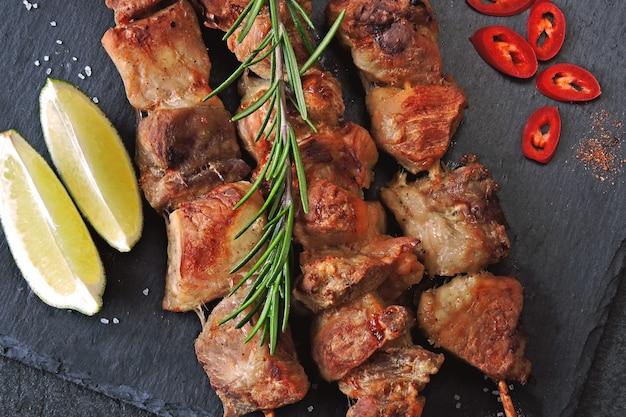 食欲をそそるケバブ、スパイス、チリ、ライム。石の板に香ばしい豚の串焼き。