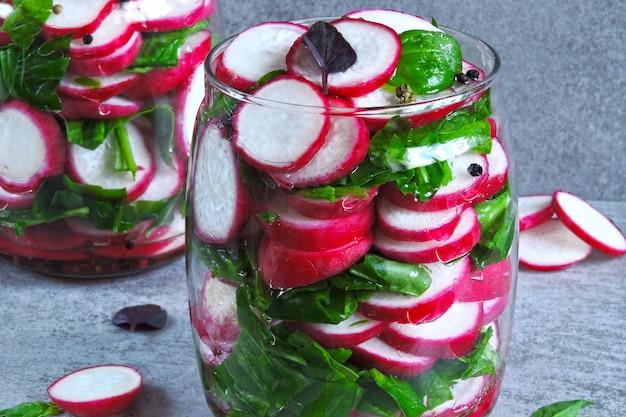 ほうれん草入りの大根サラダ。瓶の中の新鮮な野菜のフィットネスサラダ。野菜の発酵。