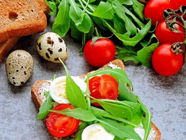 Пшеничные ржаные гренки с рукколой, перепелиными яйцами и помидорами черри.