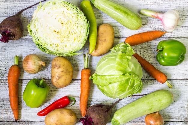 Закройте вверх различных красочных сырцовых овощей на белом деревянном столе.