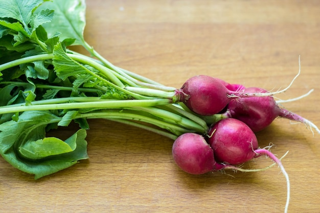 Букет из красной редьки с садовой кровати на сельском столе