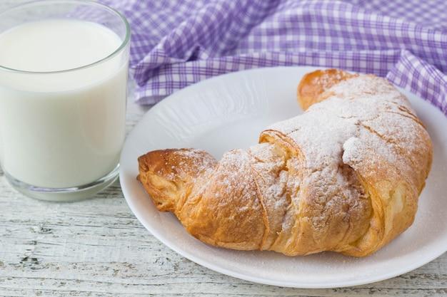 朝食の背景に古い木製のテーブルに牛乳とクロワッサン。