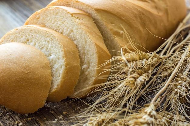木製のテーブルのクローズアップに小麦の穂でスライスされたパン
