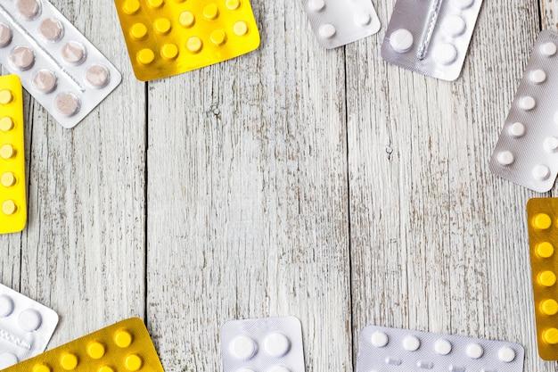 薬の境界線。ビタミン、錠剤、白い木製のブリスターパックの丸薬