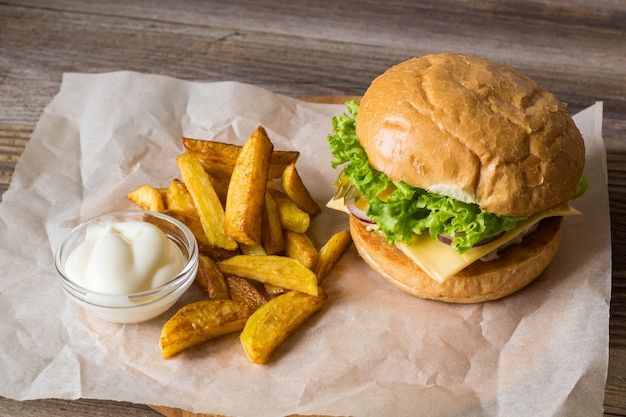 自家製ハンバーガー、チキン、オニオン、キュウリ、レタス、チーズ、ポテトフライ付きの木製テーブル