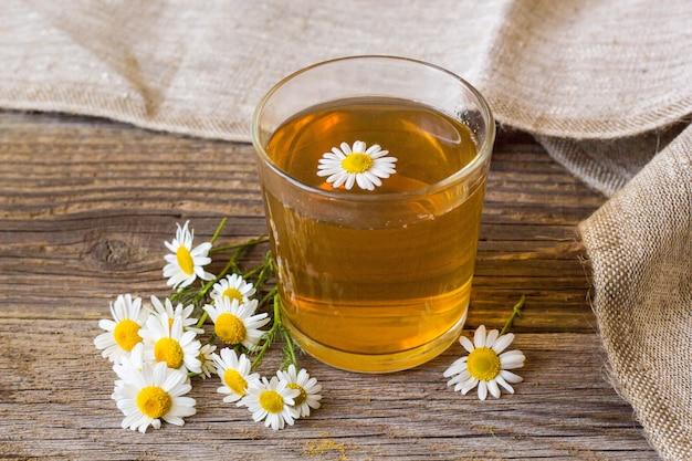 素朴な木製の背景にカモミールの花と紅茶のカップ