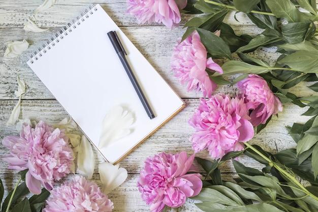 空白のメモ帳、ペン、および白い木製のテーブルに牡丹を開きます。ロマンチックなフラットレイアウト。