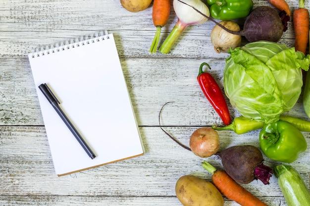 新鮮なジューシーな野菜の境界線、空白の白いメモ帳、白い木製の背景、上面にペン。