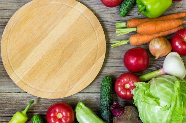 サークルまな板と木製の背景で野菜。健康的な食事
