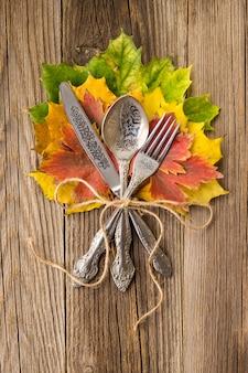 素朴な木の板にカラフルなカエデの葉と感謝祭の休日の秋の夕食の場所の設定