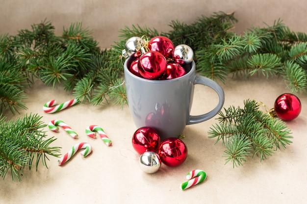モミの木のクリスマス背景とカップで銀と赤のクリスマスデコレーションボール