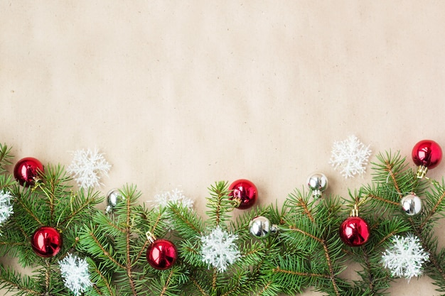 モミの枝に赤と銀のボールと素朴なベージュ色の背景に雪の結晶のお祝いクリスマス国境