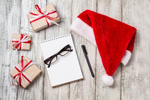 コピースペース付きのクリスマスアイテムとビジネスアイテムサンタキャップメモ帳ペングラスと装飾ギフトボックス