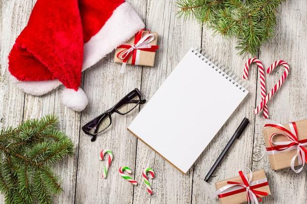 コピースペース付きのクリスマスアイテムとビジネスアイテムは、サンタキャップメモ帳ペンメガネと装飾ギフトボックスとモミの木をトリミング