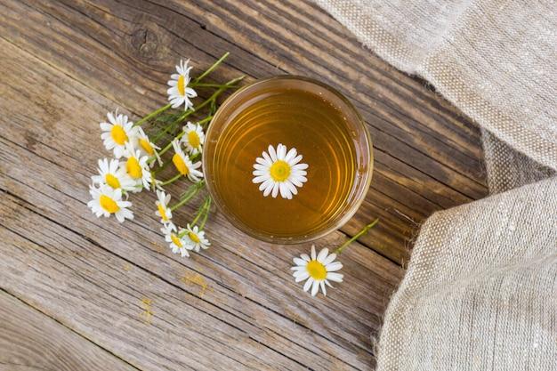 素朴なテーブルにカモミールの花とお茶のカップ